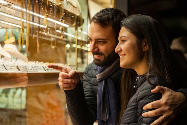Couple looking at the showcase of an outdoor jewelry. Premium Photo