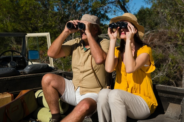Couple looking through binoculars Free Photo