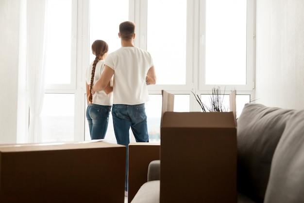 Пара смотрит в окно планирования будущего в новом доме Бесплатные Фотографии