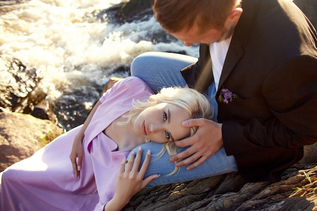 Couple in love close-up sitting on a stone on a beautiful sunny day at sunset. Premium Photo