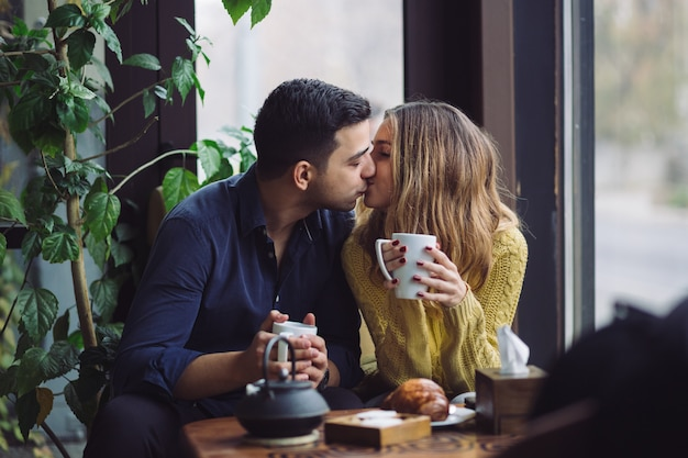 Couple in love drinking coffee in coffee shop Free Photo