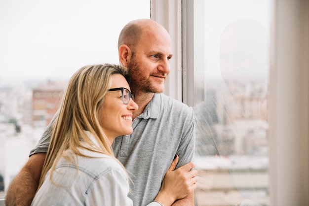 Couple in love in front of window Free Photo