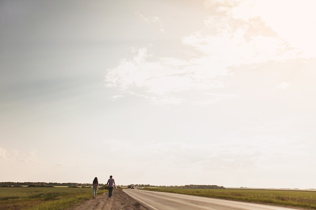 Couple in love is on a country road. the concept of hitchhiking. rear view. copy space for text. Premium Photo