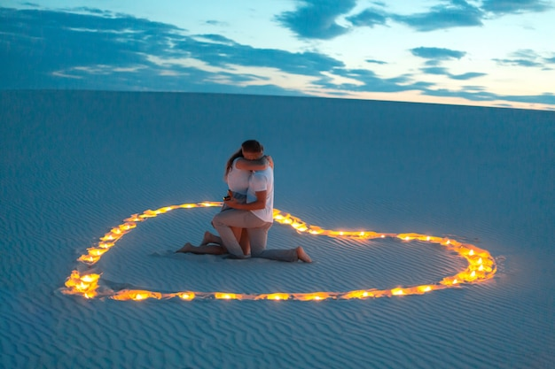 Couple in love romantic hugs in sand desert. evening, romantic atmosphere, in sand burn candles in form of heart Premium Photo