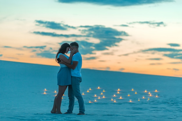 Couple in love romantic hugs in sand desert, evening, romantic atmosphere, in sand burn candles Premium Photo