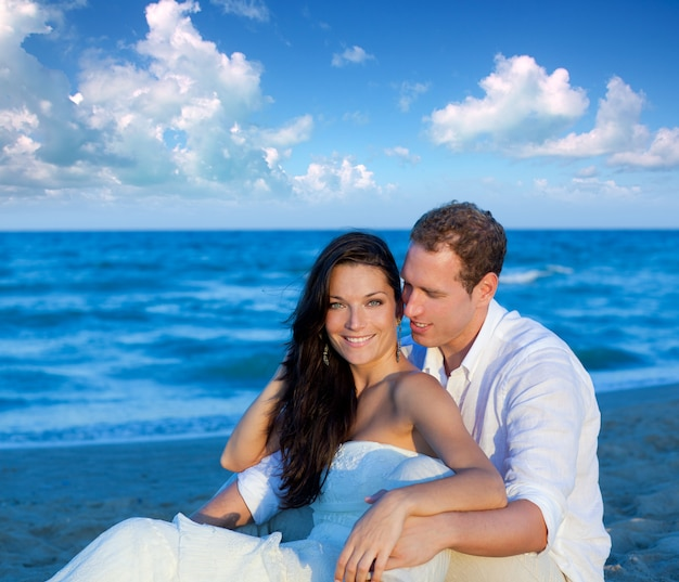 Couple in love sitting in blue beach Premium Photo