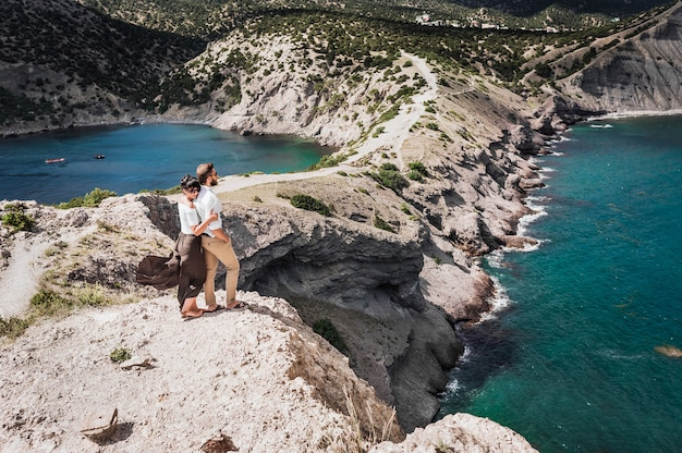 A couple in love travels. man and woman at the sea. travelers. man and woman have a rest abroad. the relationship between a man and a woman. woman hugging man. business abroad. honeymoon trip. in love Premium Photo