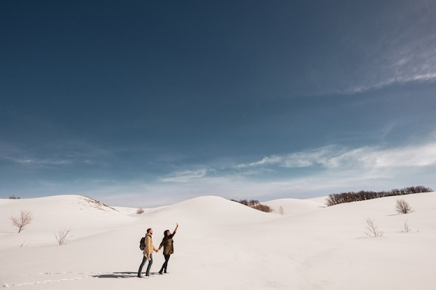 Couple in love walks in winter in the snow. man and woman traveling. couple in love in the mountains. travelers in the mountains. winter walk. winter adventures. loving couple Premium Photo