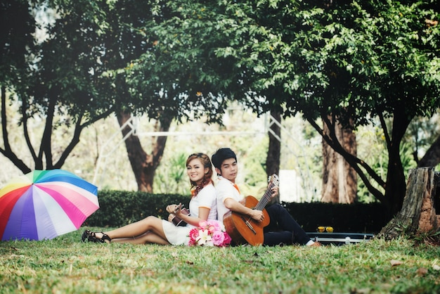Couple in love with playing guitar at nature Free Photo