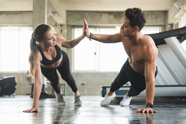 Couple love young fitness man and women workout exercise together. weight training and cardio program concept. Premium Photo