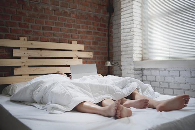 カップルの恋人はベッドで寝ています。タブレットでオンラインで映画を見る 無料写真