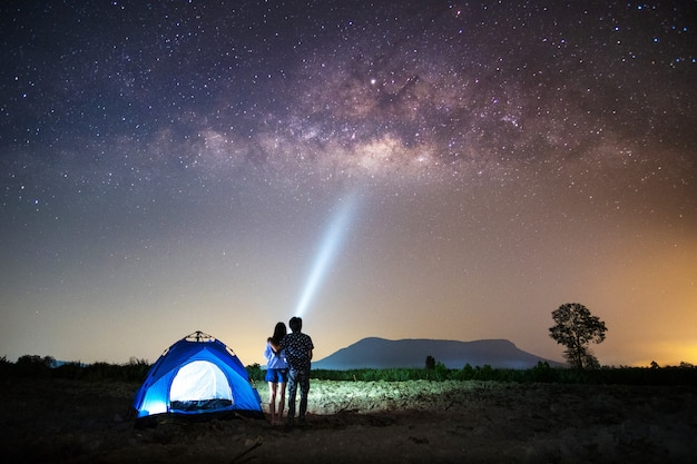 Couple lover standing near the tent and looking milky way and stars Premium Photo