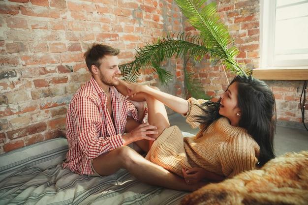 Coppia di innamorati a casa che si rilassano insieme. l'uomo e la donna caucasici che hanno fine settimana, sembrano teneri e felici Foto Gratuite