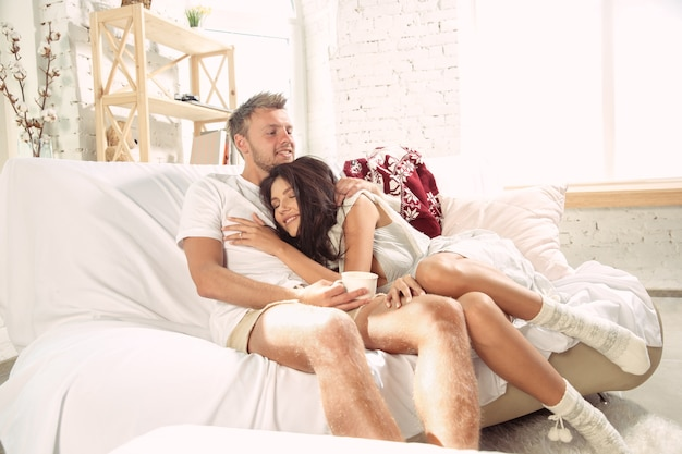 Couple of lovers at home relaxing together. Free Photo