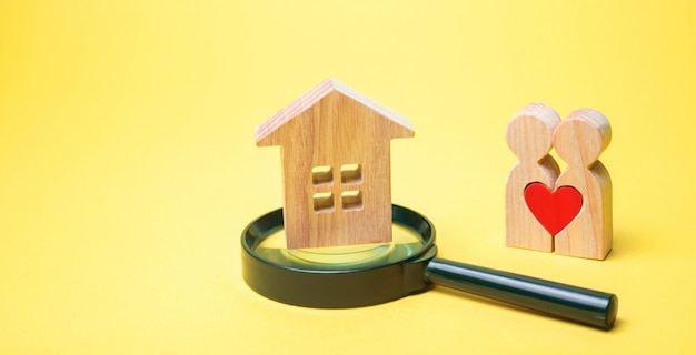 A couple of lovers is standing near the house and a magnifying glass. Premium Photo