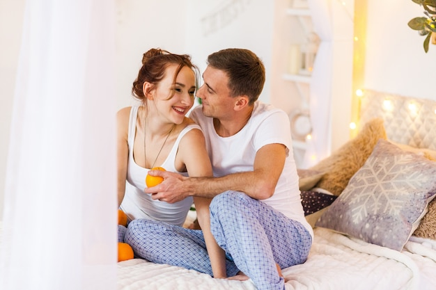 Couple of lovers in pajamas lying on the sofa. christmas time. holiday at home Premium Photo