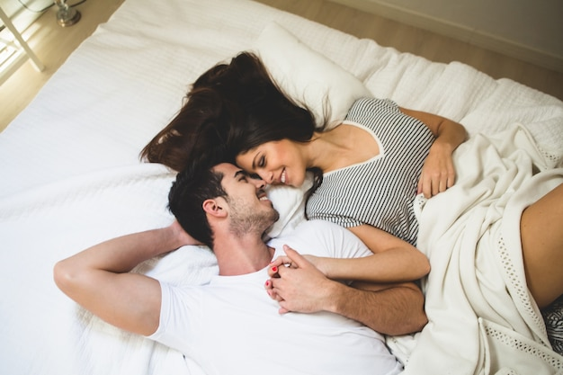 Couple lying on the bed holding hands and looking into each other's eyes Free Photo