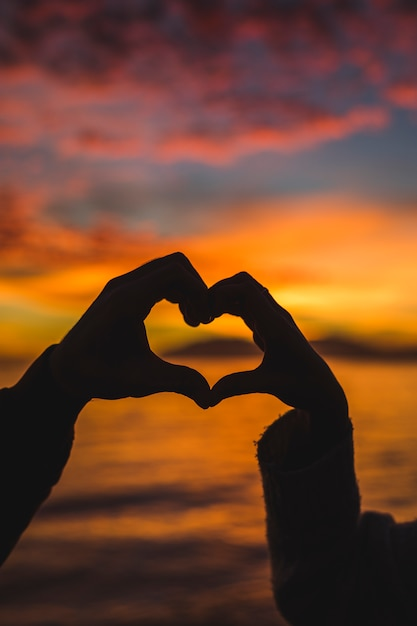 Couple making heart from hands on sea shore Free Photo