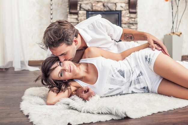 Пара мужчина и женщина обнимаются дома, лежа на ковре Premium Фотографии