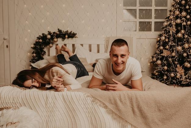 Пара мужчина и женщина лежат на кровати в спальне возле елки Premium Фотографии
