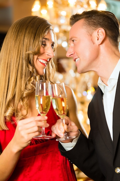 Couple, man and woman, drinking champagne in a fine dining restaurant, each with glass of sparkling wine in hand Premium Photo
