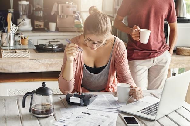 Пара, вместе управляющая внутренним бюджетом. молодая женщина в очках держит ручку во время расчетов с помощью калькулятора и ноутбука Бесплатные Фотографии