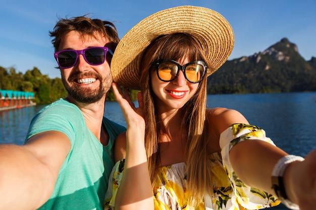 スタイリッシュな服やアクセサリーを身に着けて、素晴らしい湖と山の景色の近くで自分撮りをマークするカップル。遊び心のある幸せな雰囲気。 無料写真