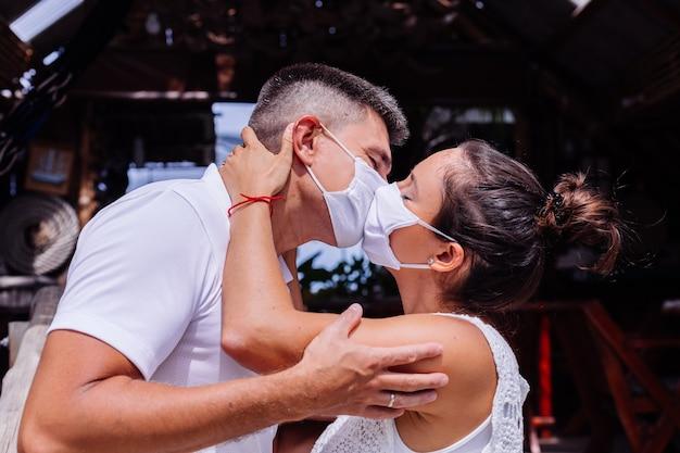 Coppia in maschere mediche bianche in vacanza stare fuori dall'hotel e baciare Foto Gratuite