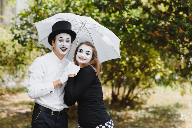 A couple of mimes walk along the pavement under umbrellas. Premium Photo