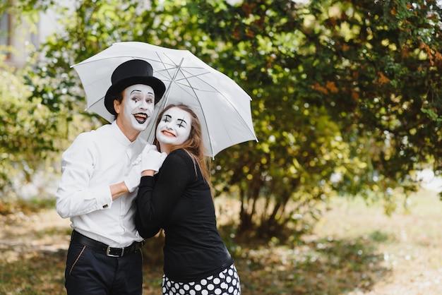 A couple of mimes walk along the pavement under umbrellas. Premium Photo