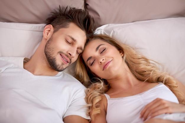 Coppia sonnecchiare in camera da letto Foto Gratuite