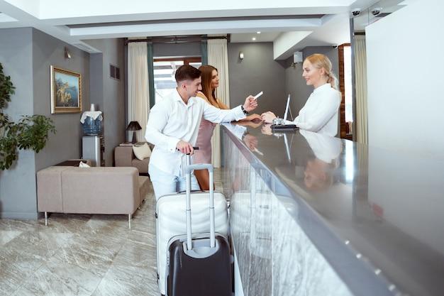 Couple near reception desk in hotel Premium Photo