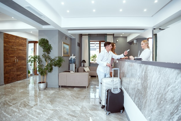 Couple near reception desk in hotel Premium Photo
