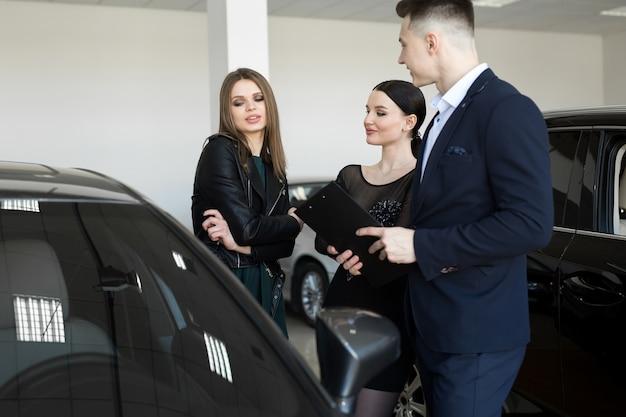 Пара друзей женщин с автосалоном выбирают машину в автосалоне Premium Фотографии
