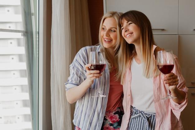 窓を見て、グラスワインを持っている幸せなのんきな女性のカップル。居心地の良い家庭的な雰囲気。 無料写真