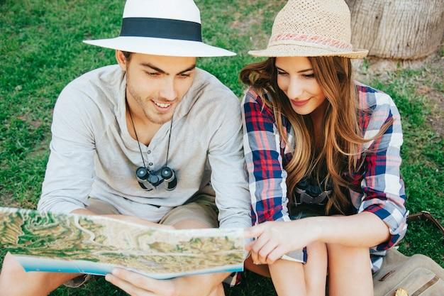 Пара счастливых путешественников на траве Бесплатные Фотографии