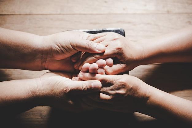 夫と妻のカップルが手を繋いでいるとあなたのテキストのコピースペースを持つ木製のテーブルで一緒に祈る 無料写真