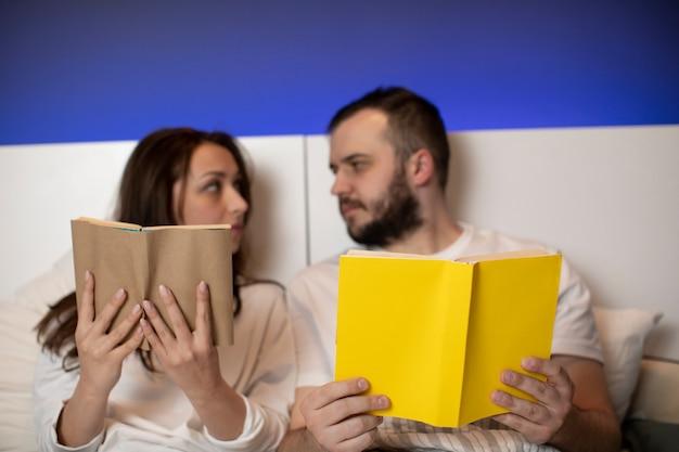 Пара влюбленных хранит свои книги в постели, глядя друг на друга Premium Фотографии