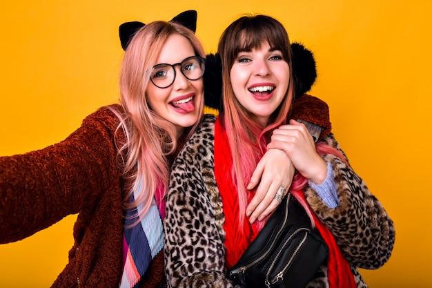 かなり面白い流行に敏感な親友の妹の女の子が黄色の壁でselfieを作り、舌を見せて笑顔で、トレンディな春の毛皮のコート、スカーフ、お尻のバッグ、透明なメガネを身に着けています。 無料写真