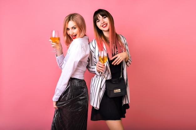 Пара из двух довольно забавных элегантных женщин, пьющих шампанское в конце, наслаждаясь вечеринкой, элегантные гламурные черно-белые наряды, модные розовые волосы Бесплатные Фотографии