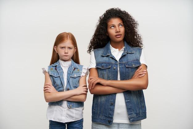 Coppia di giovani ragazze carine offese in posa su bianco, tenendo le mani giunte e in piedi con facce dispiaciute, litigando e non vogliono parlare tra loro Foto Gratuite