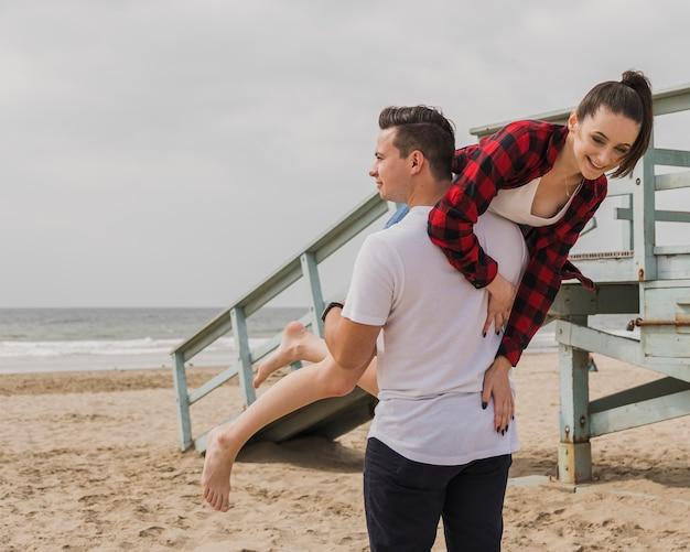 愚かなポーズのビーチをカップルします。 無料写真