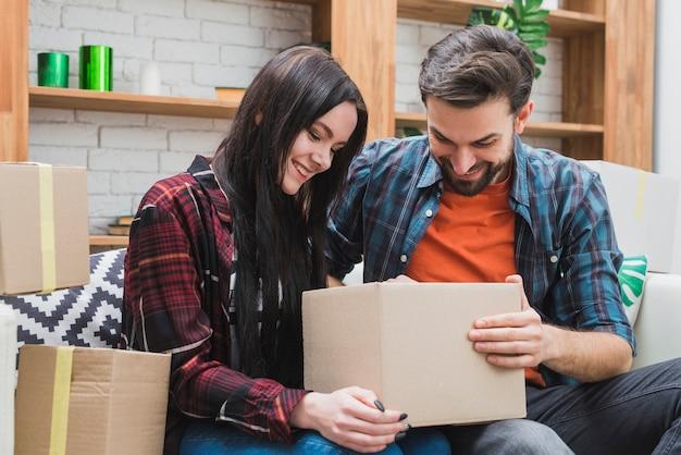 Couple opening parcel on sofa Free Photo