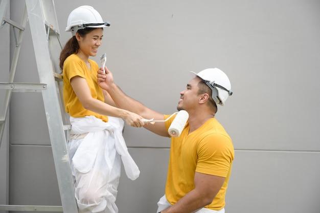 Пара красит стену Premium Фотографии