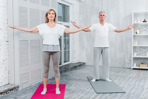 Couple performing yoga by outstretching arms standing on yoga mat Free Photo