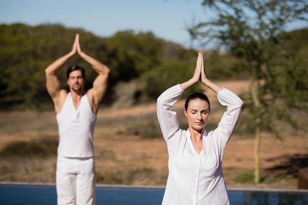 Couple performing yoga at safari vacation Free Photo
