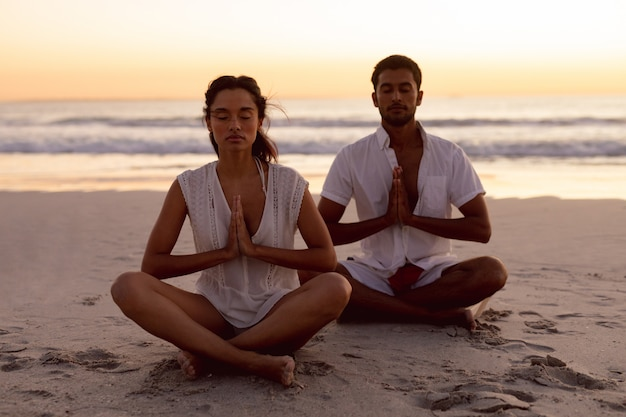 Couple performing yoga together on the beach Free Photo