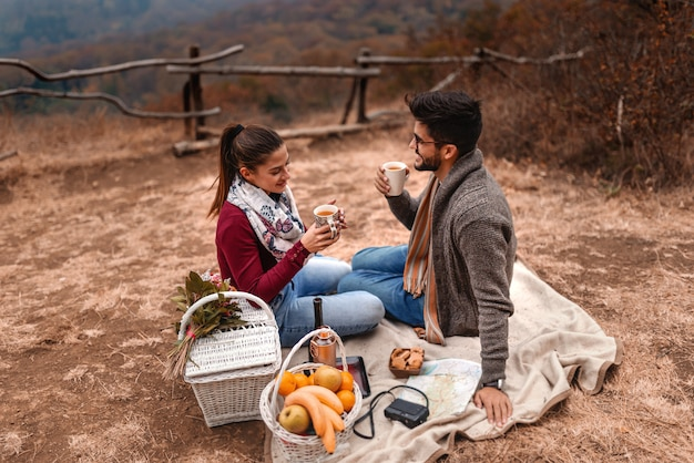 Couple at picnic sitting on blanket and drinking tea in nature. autumn time. Premium Photo