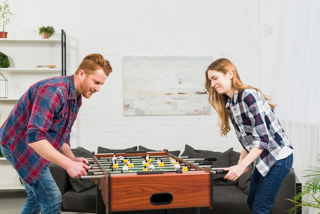 Couple playing football table soccer game at home Free Photo