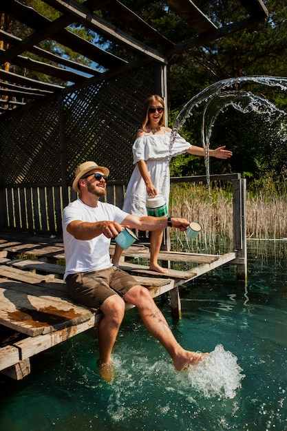 Couple playing and man sitting with feet in water Free Photo